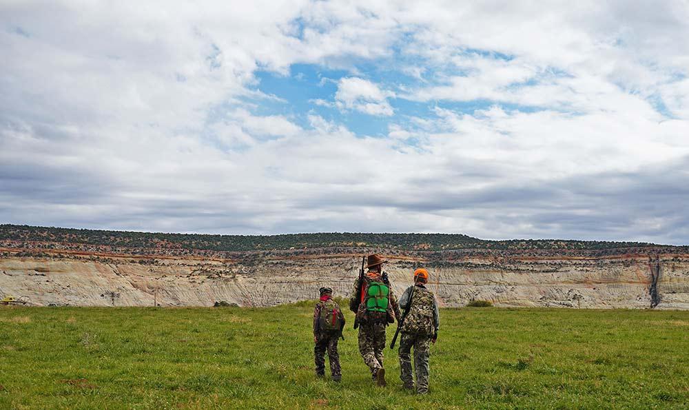 hunter and kids walking through field