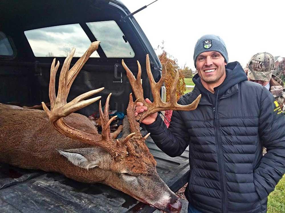 hunter standing next to giant buck