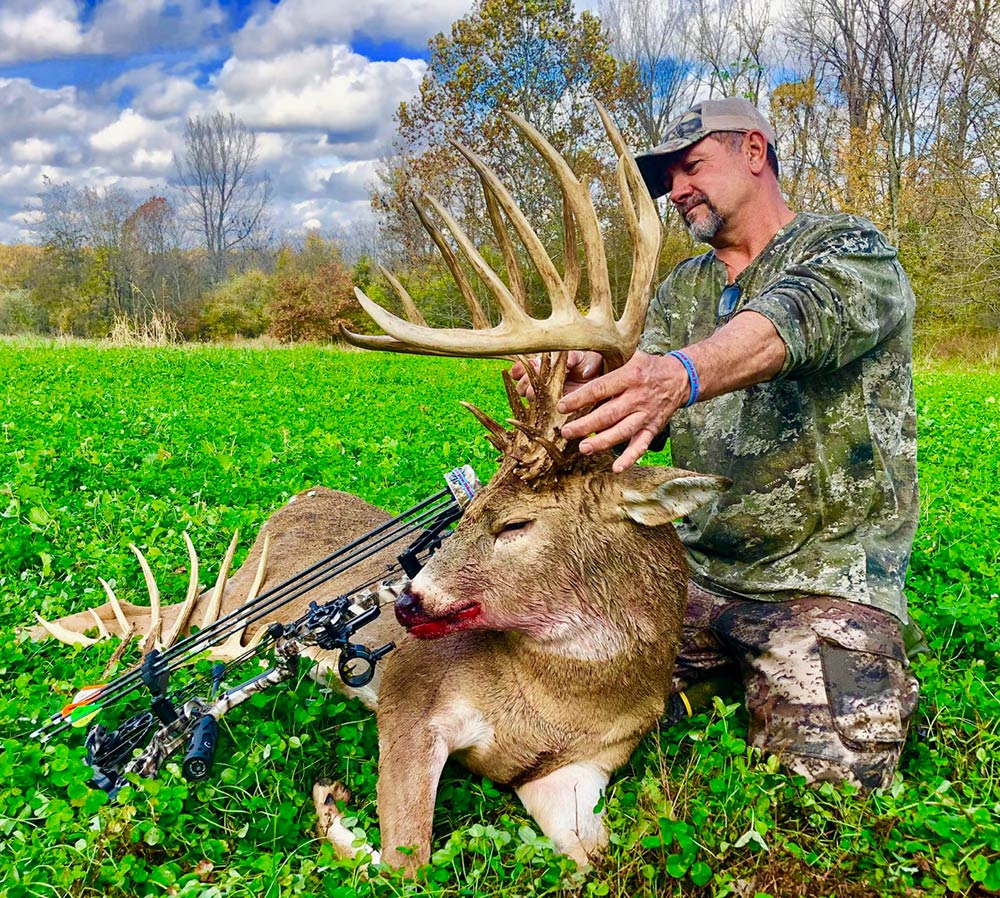 male hunter kneeling next to giant buck