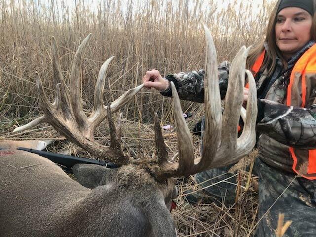 female hunter next to giant buck