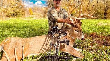 male hunter beside giant buck