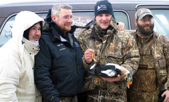 four men holding a king eider