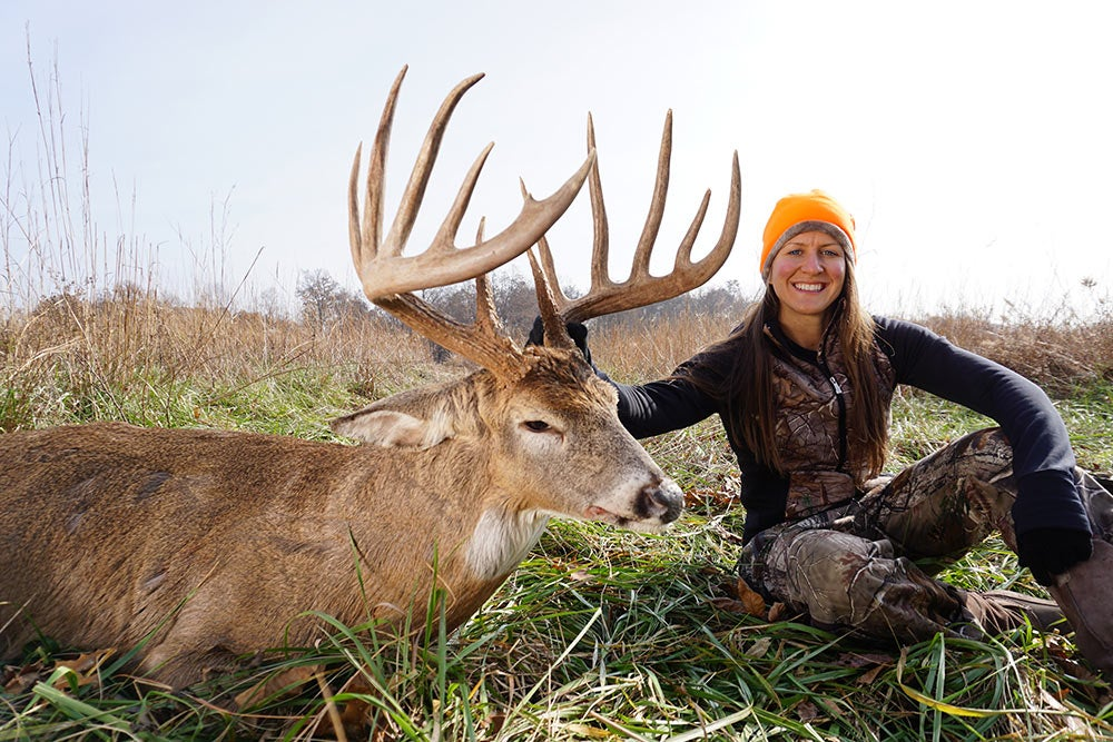 female hunter next to giant buck