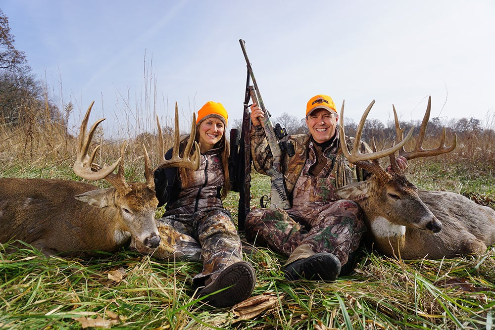 father and daugher beside their two giant bucks