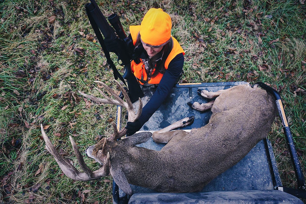 top down view of a female hunter beside a giant buck