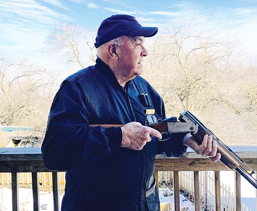 Older man with blue cap and coat holding break-action shotgun, cracked open, ready to shoot on a winter's dday