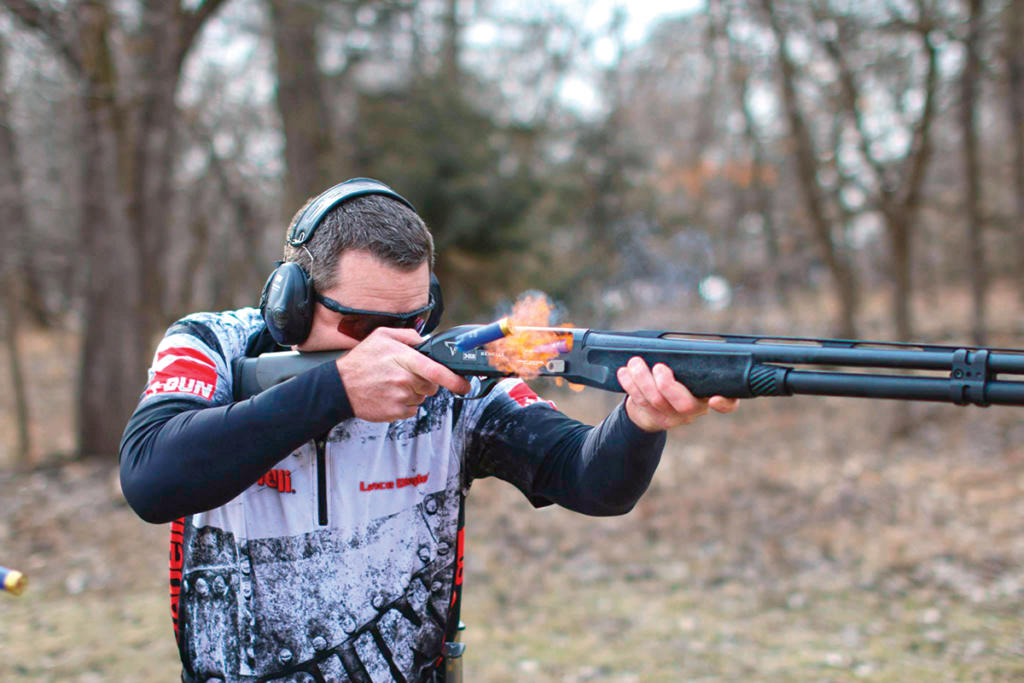 Competition skeet shooter with black semi-auto shotgun, fire, and shells ejecting from the action.