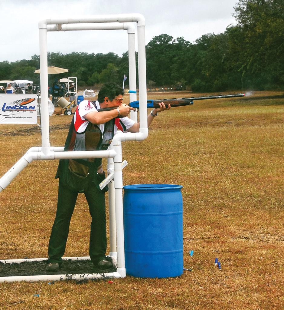Woman shooting skeet at a pvc-pipe station, shooting vest, white shirt, blue range barrel