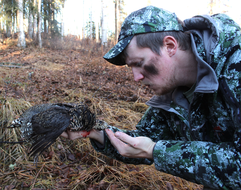 A satirical photo of a hunter with a dead grouse.