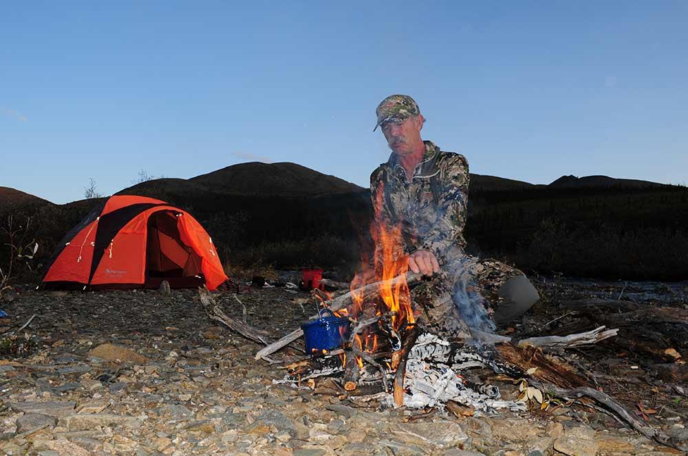 hunter tending a fire at an alaskan hunt