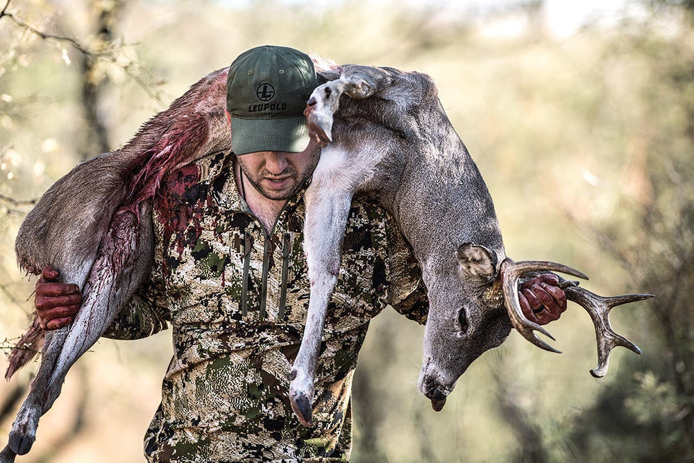 hunter hauling coues deer over his shoulders