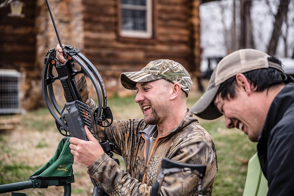 two hunters laughing and testing crossbows