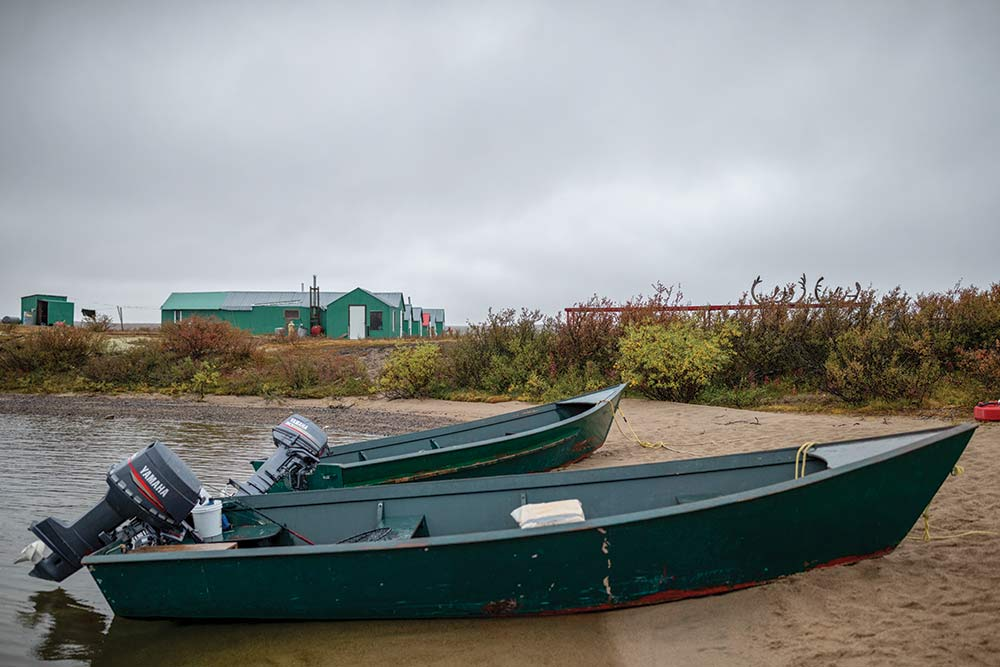 two boats sitting on a shore at hunting camp in quebec
