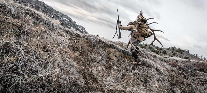 hunter carrying elk antlers up a hillside