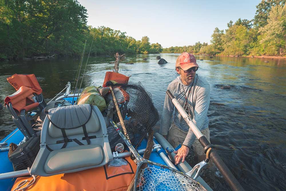 angler walking raft through river