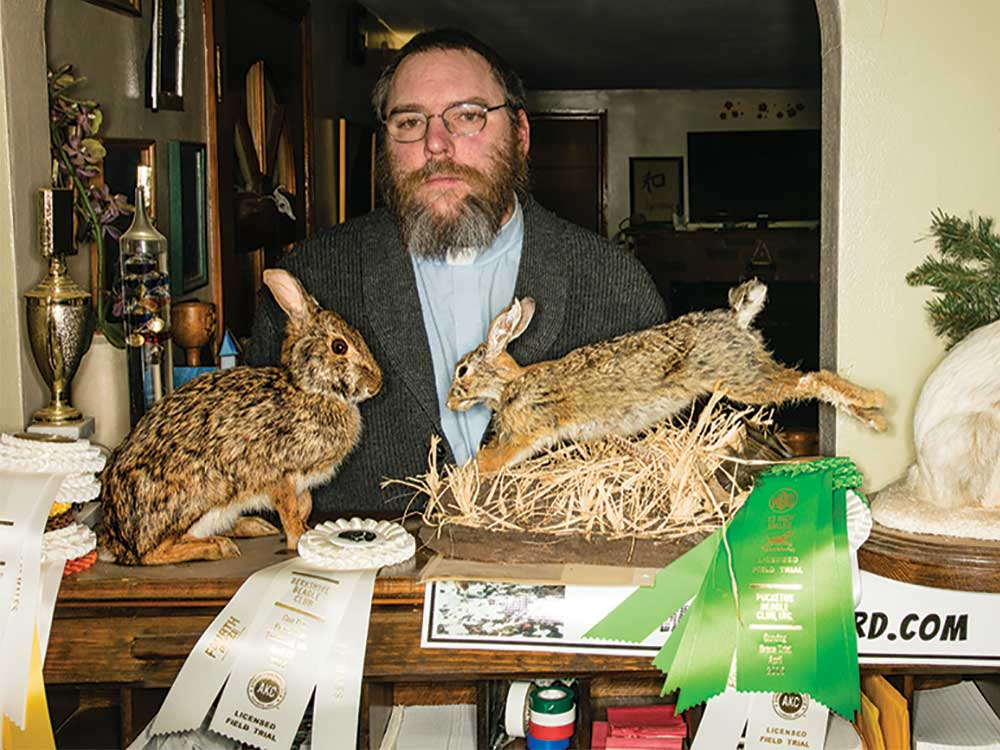 pastor rabbit hunter behind two stuffed rabbits