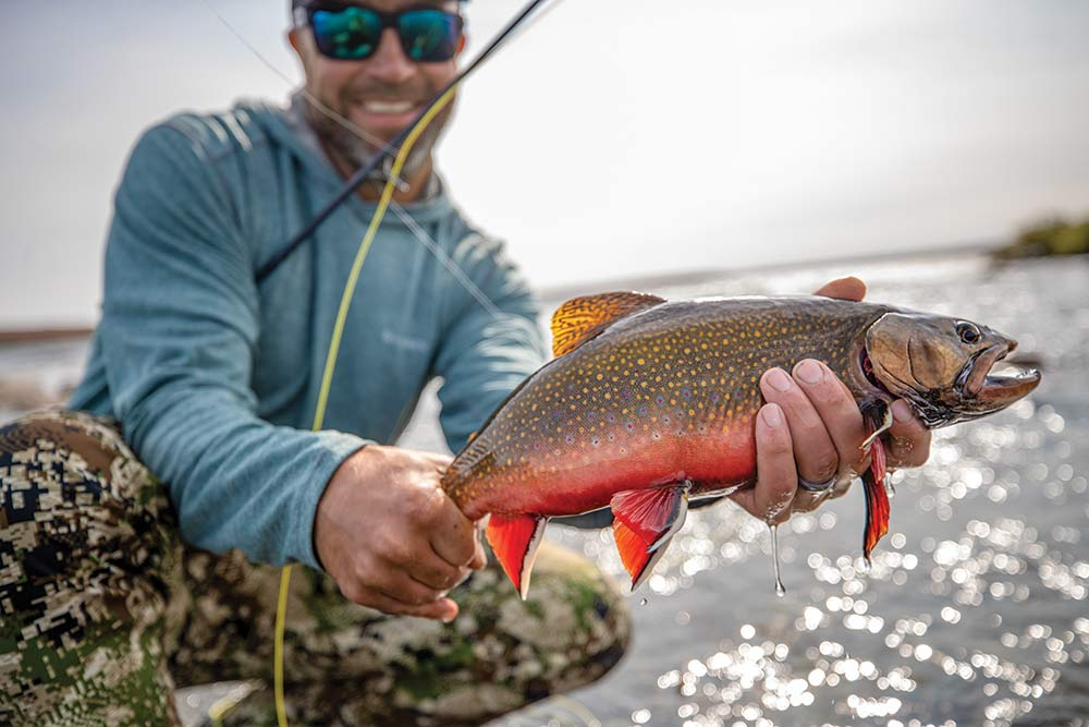 fisherman holding up a brook trout