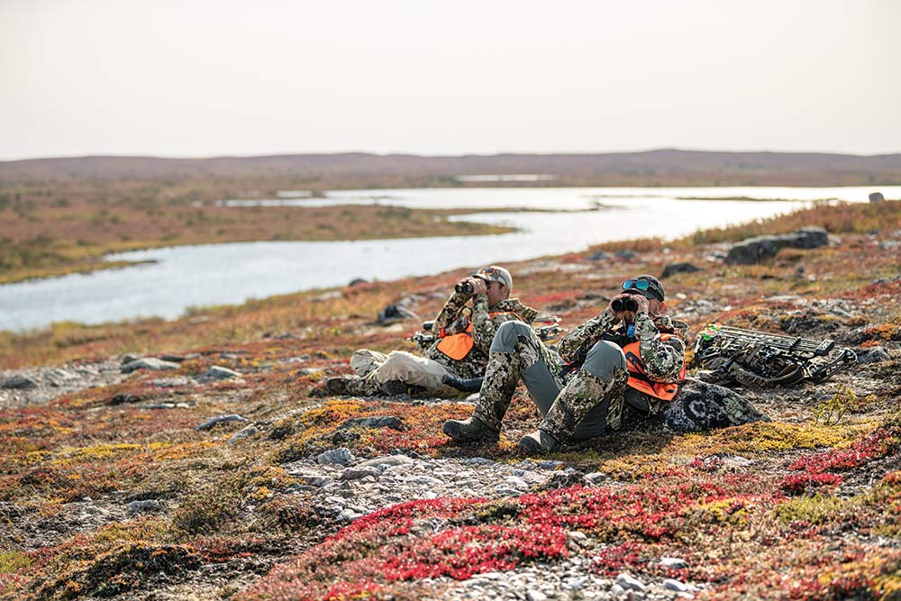 two hunters surveying canadian tundra