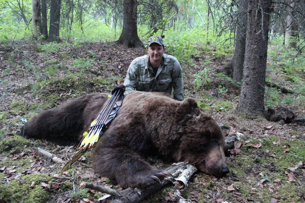 a hunter kneeling next to a bear