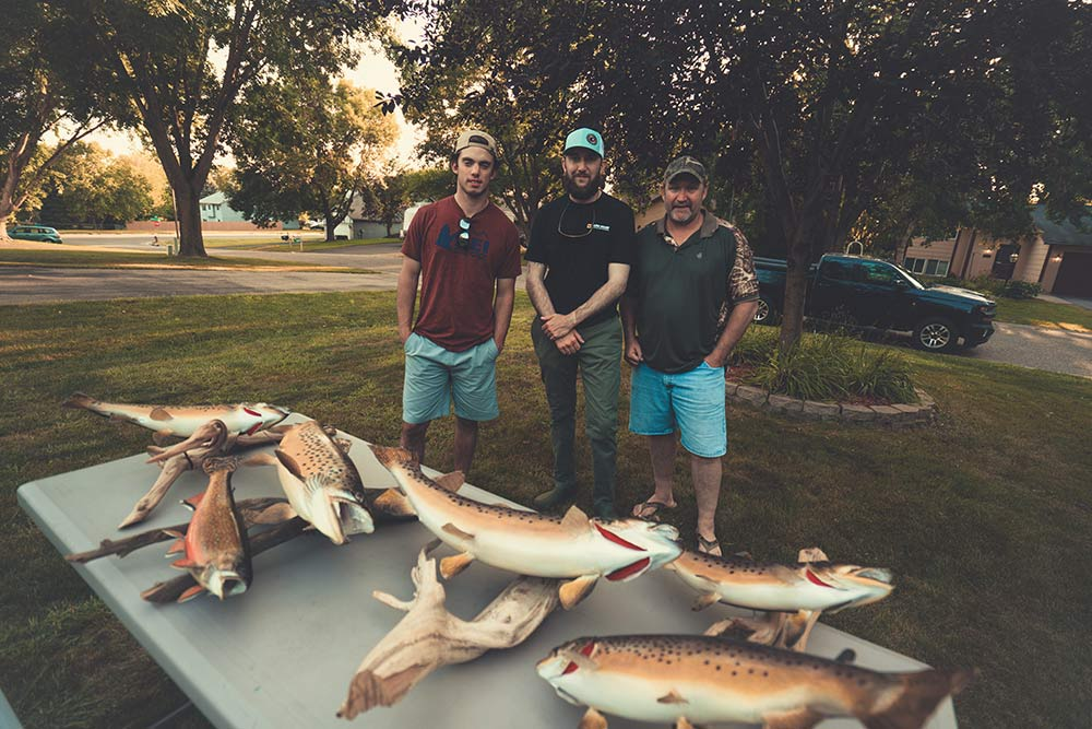 three men standing behind trout trophies