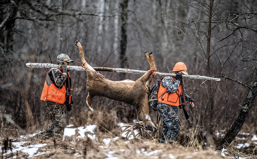 two hunters hauling whitetail through woods
