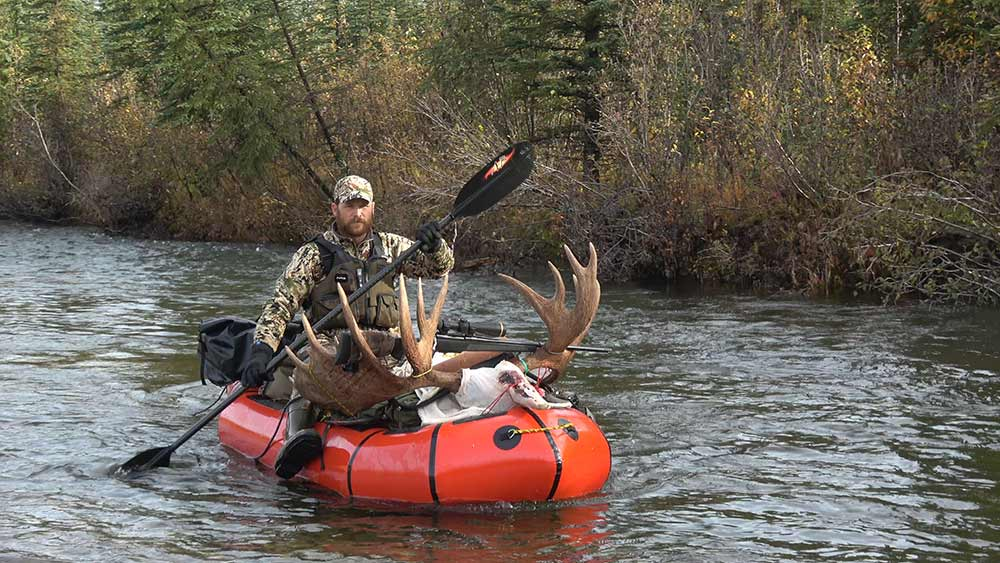 hunter using paddles on a packraft