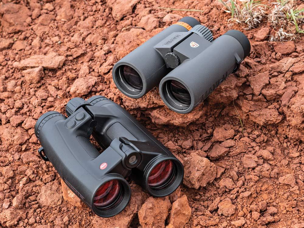 two pairs of binoculars sitting on rocks