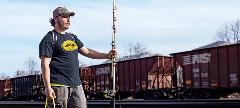angler holding a fishing pole with a train in the background