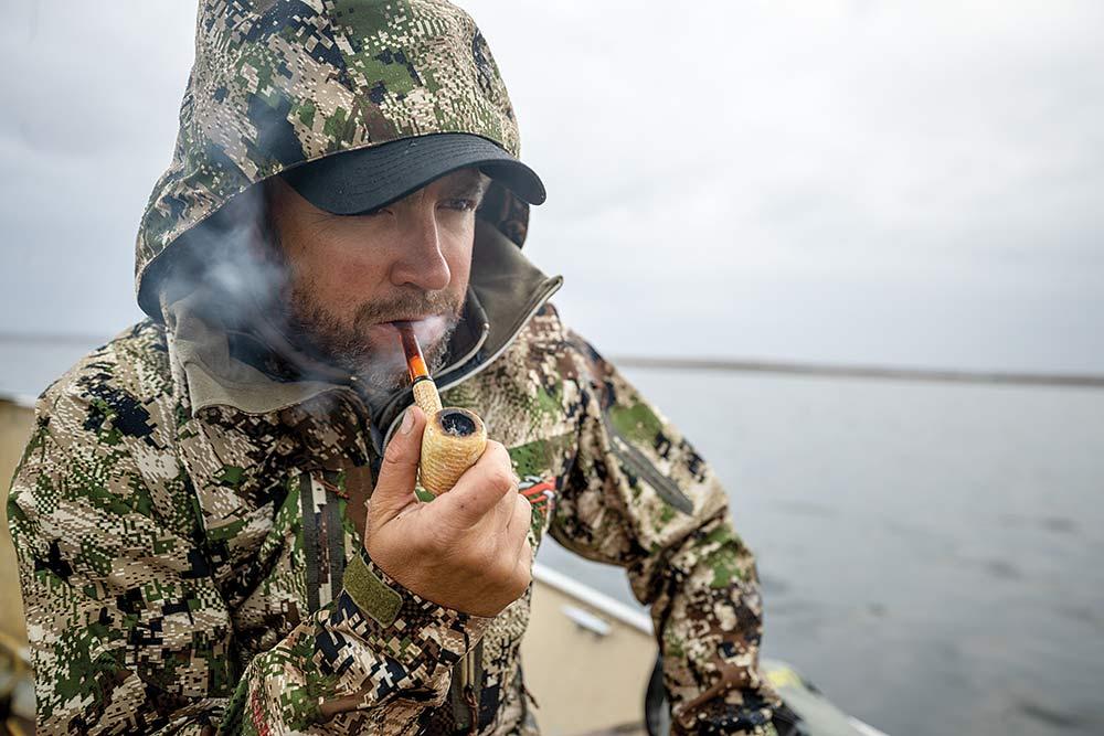 man wearing camouflage smoking a pipe