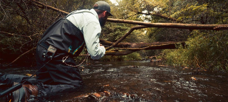 angler kneeling while trout fishing the Driftless Area