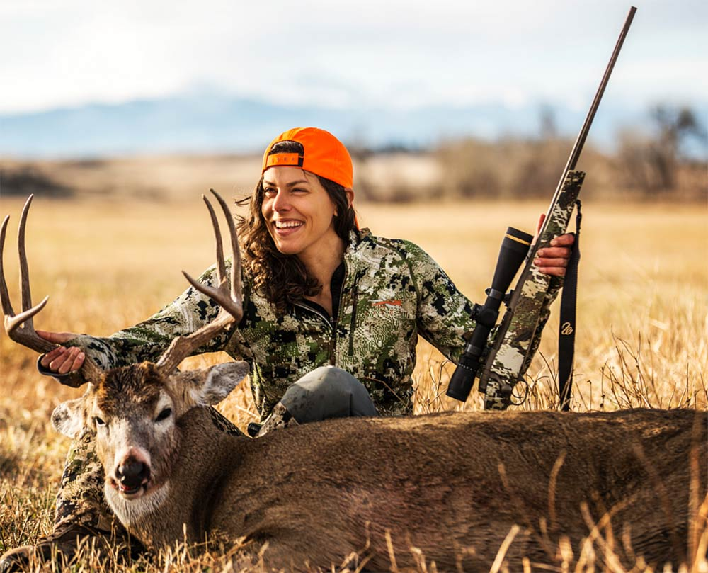 female hunter holding rifle kneeling next to a buck