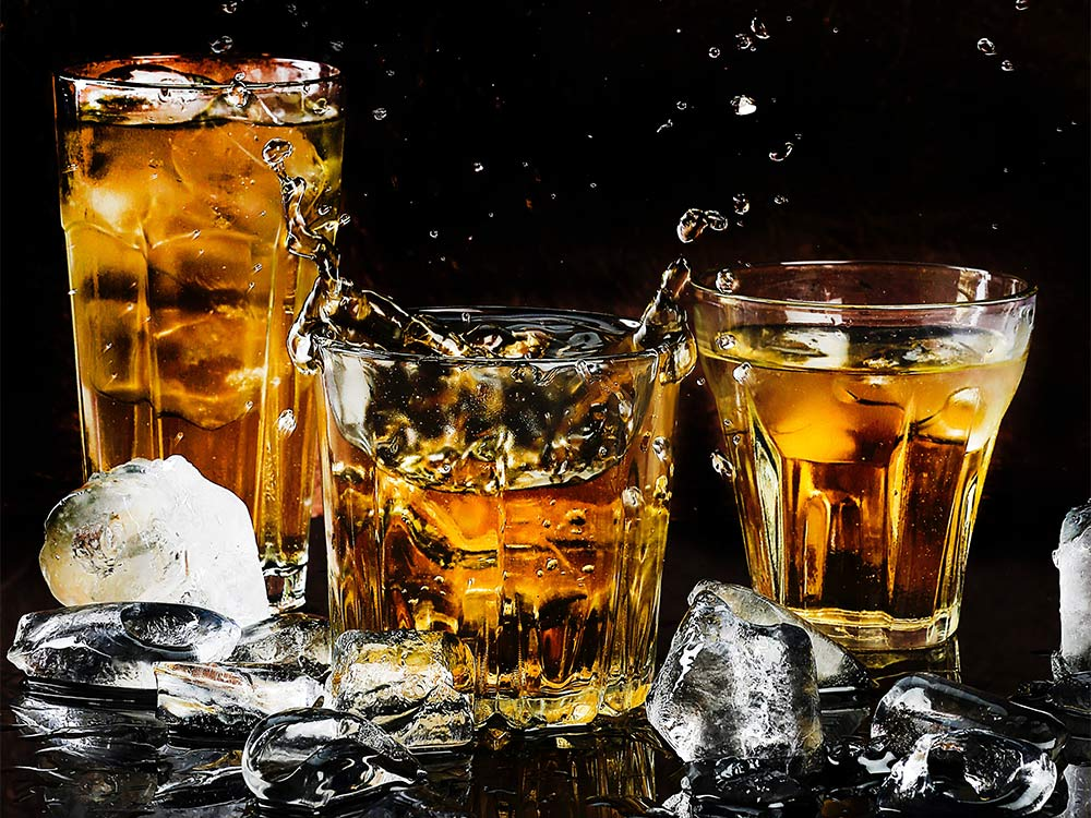 three glasses of bourbon with ice