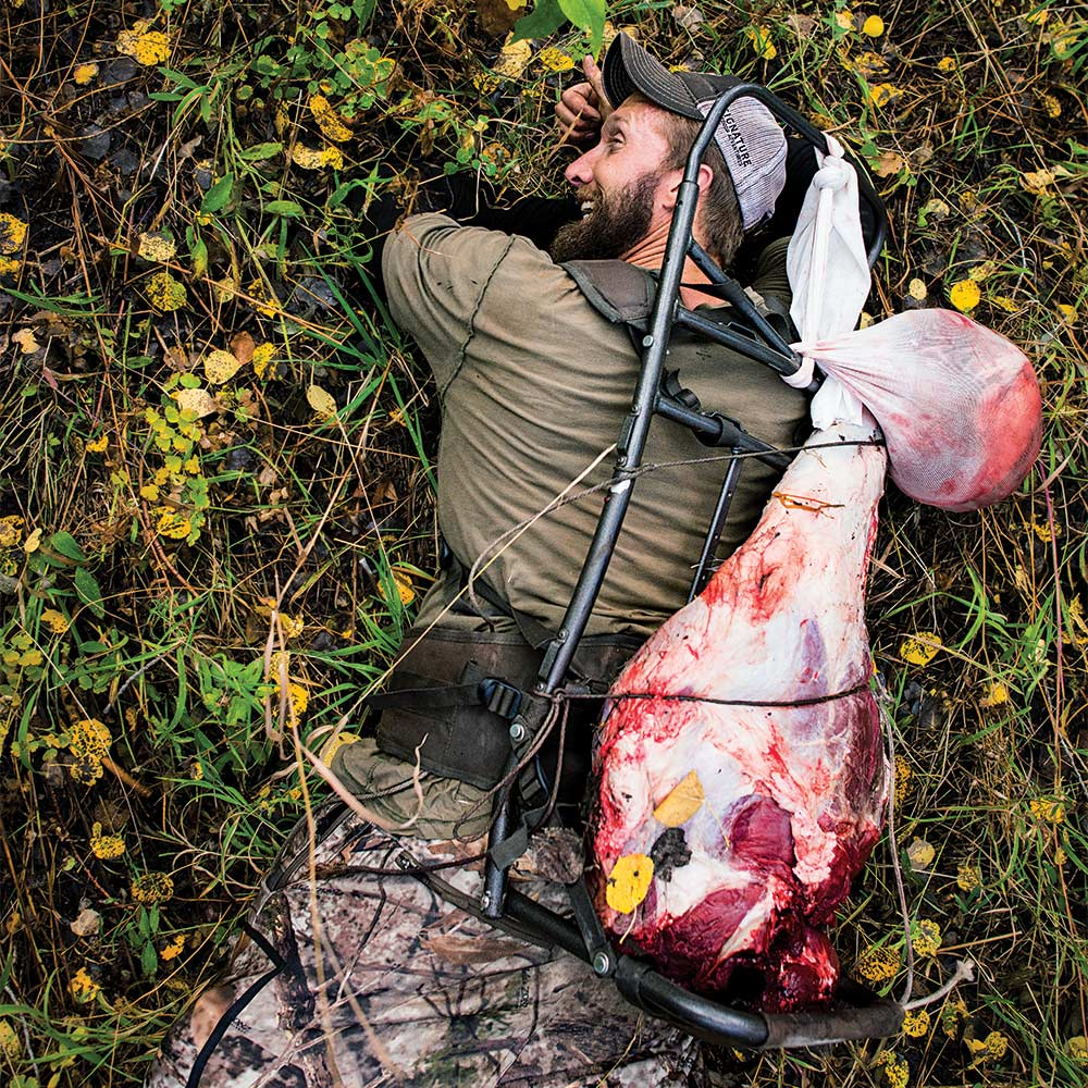 hunter on ground carrying elk meat