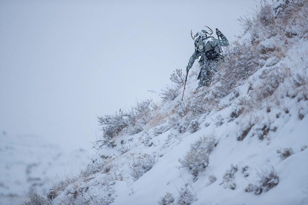hunter hauling whitetail up snow hillside