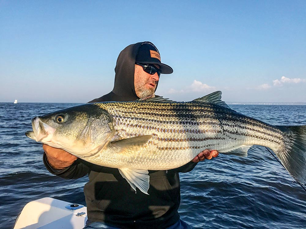 eric kerber holding a striped bass