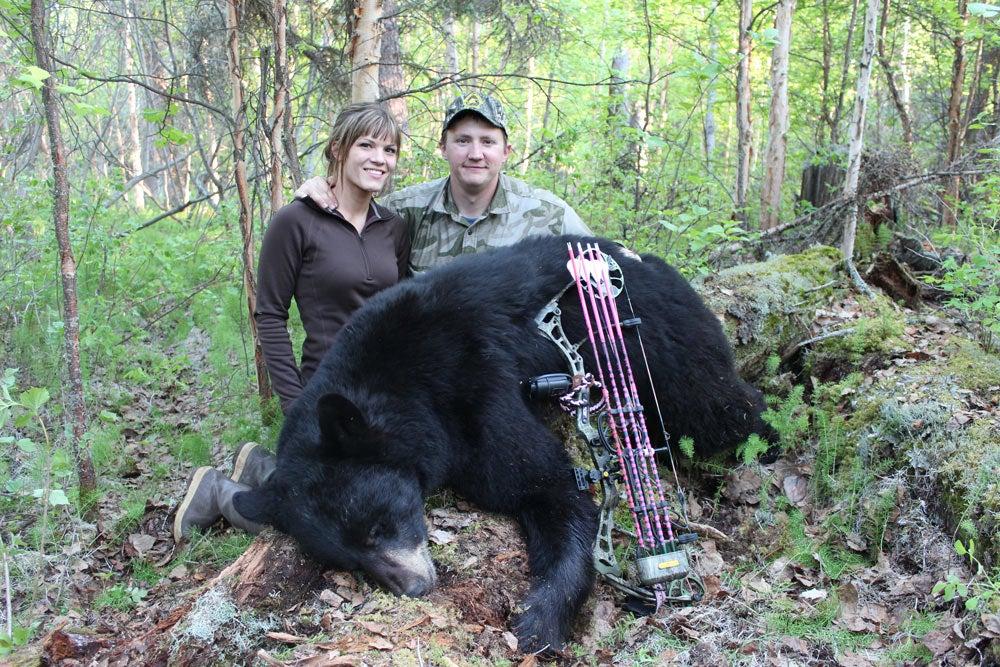 man and woman bowhunting a black bear