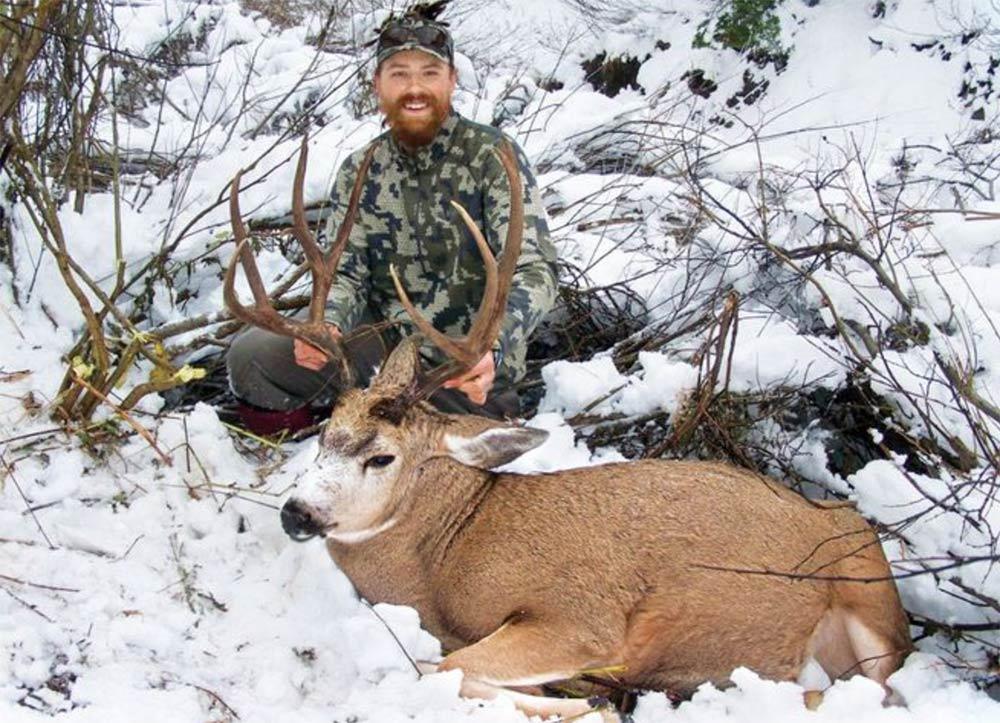 hunter with deer in snow