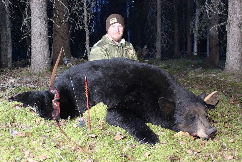 hunter kneeling next to a bear
