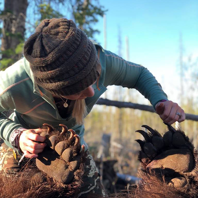 hunter checking bear claws