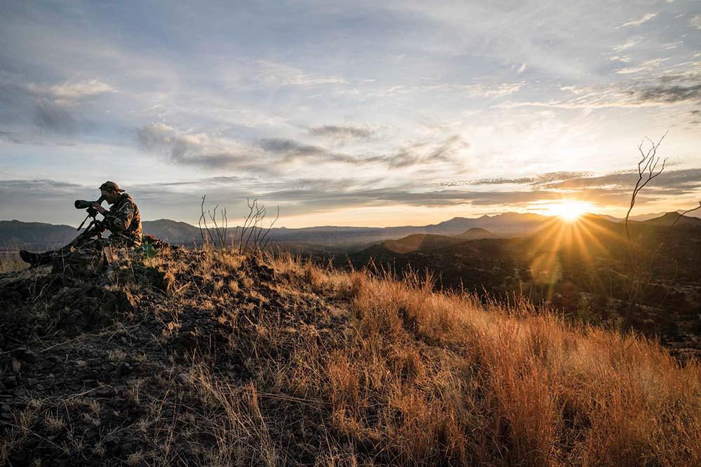 sun cresting a mountain hillside