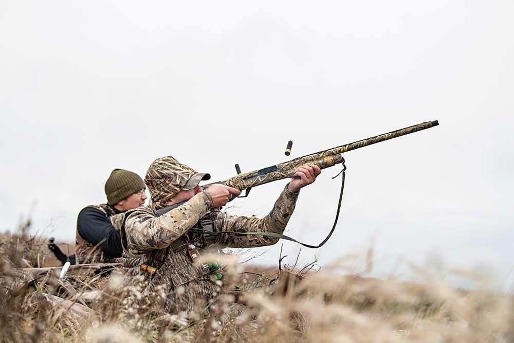 hunter aiming shotgun in field