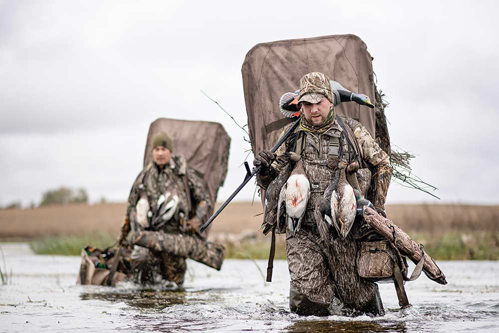 two hunters wading through water carrying duck gear