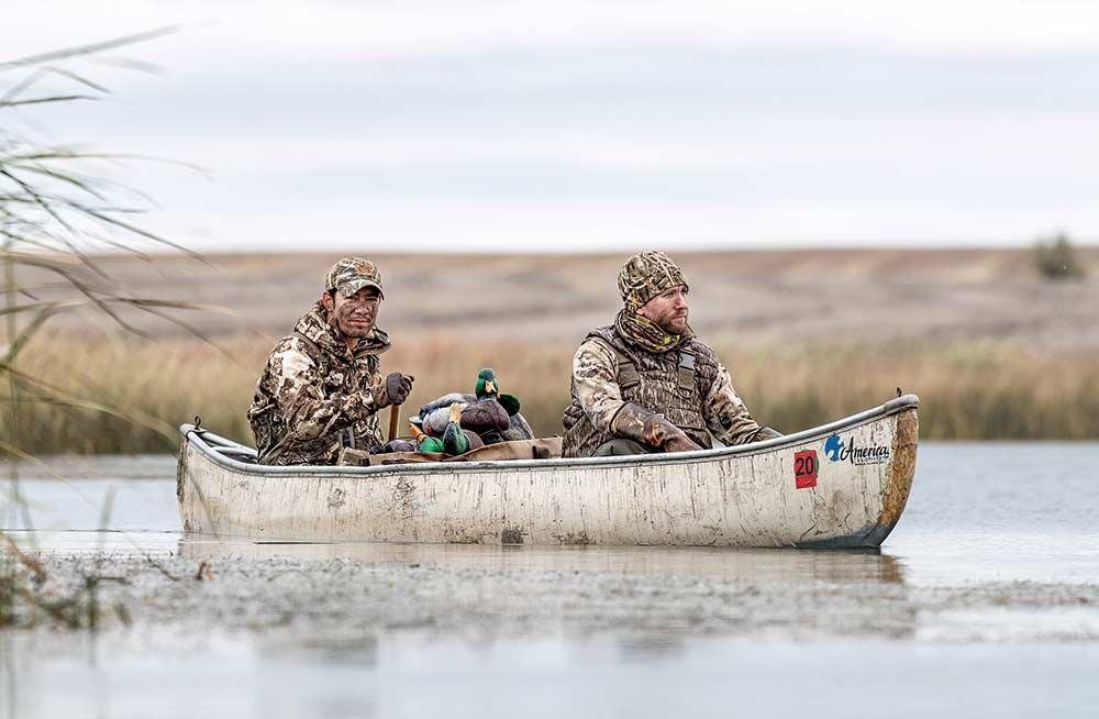 two waterfowl hunters in a canoe