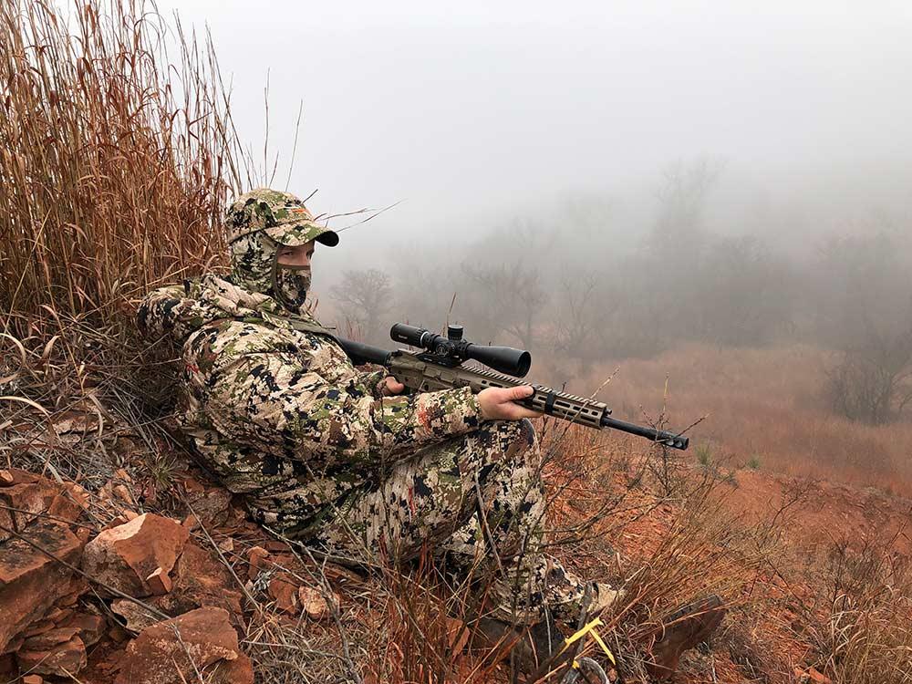 hunter leaning against brush