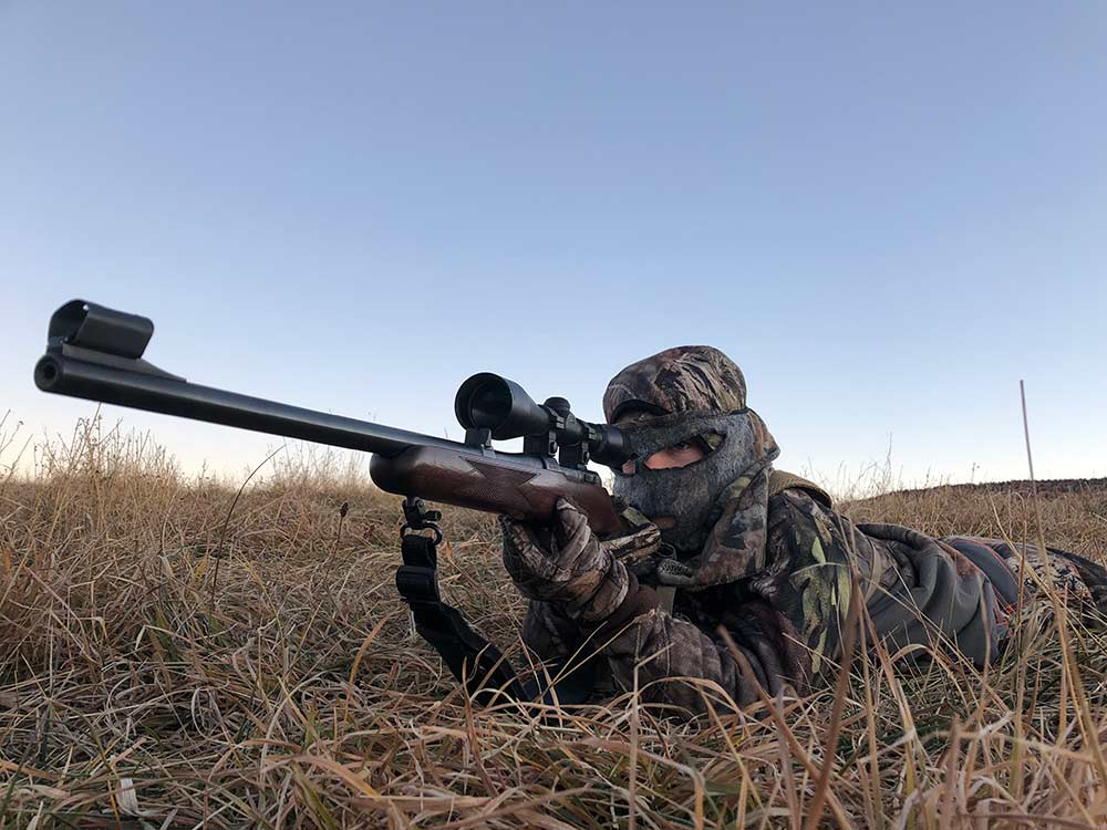 young hunter aiming rifle while laying on the ground