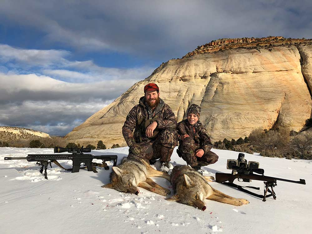 father and son kneeling behind coyote