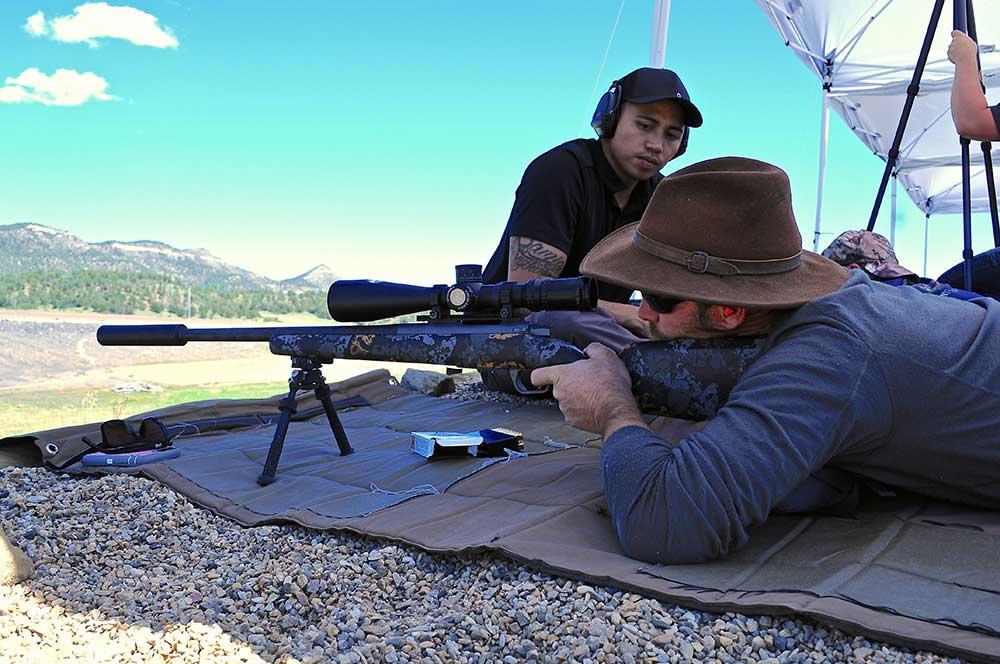 man aiming long range rifle at shooting class