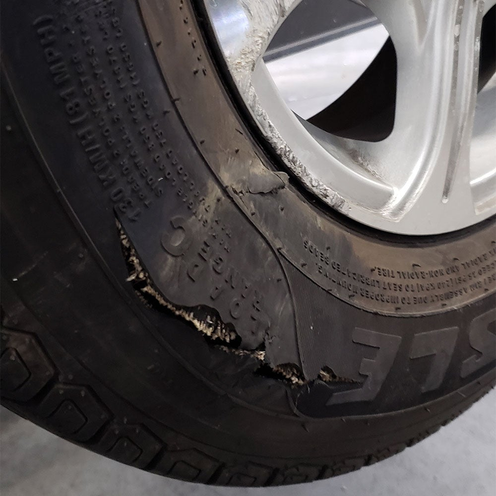 a trailer tire with a dry rotted tear