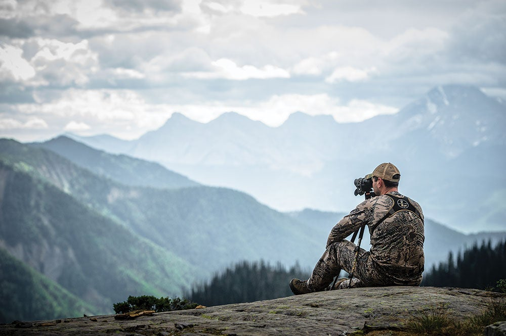 hunter in british columbia using a spotting scope for bear hunting