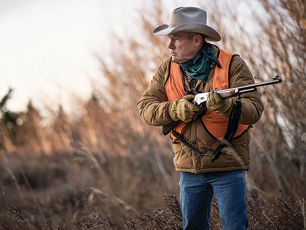 hunter in an orange hunting vest while holding a rifle